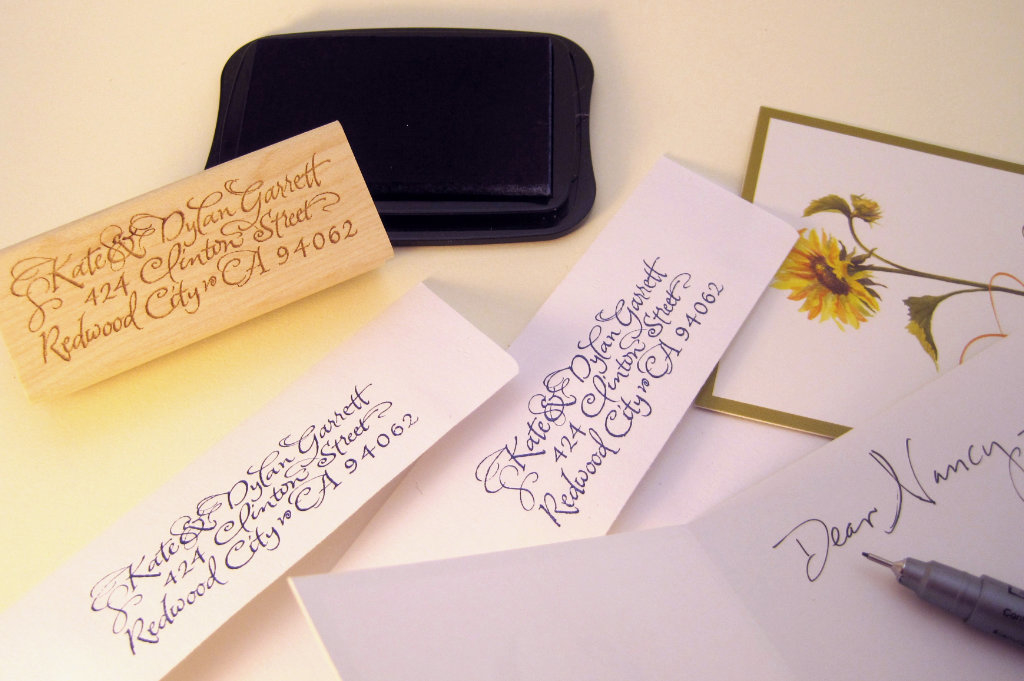 A custom calligraphy address stamp shown with envelopes