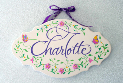 A custom decorative board with a baby's name, Charlotte, with calligraphy and paintings